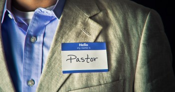 "Stock photo of someone wearing a blazer and button down shirt with a nametag that reads ""Hello my name is PASTOR"""