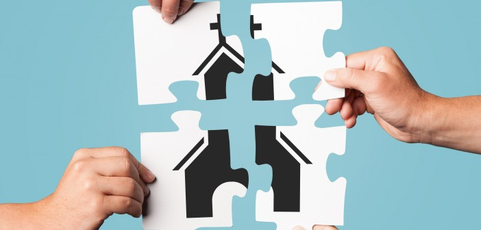 Stock photo of four individuals putting a puzzle together that depicts a church