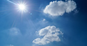 Stock photo of a clear, sunny sky with two fluffy clouds