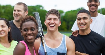 Stock photo of a mixed gender and mixed race group of young people after a pickup baseball or softball game