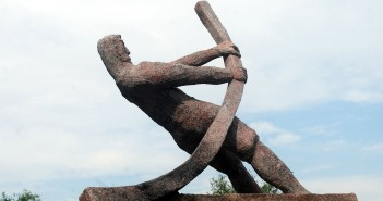 Stock photo of a statue of a man bending a metal pipe