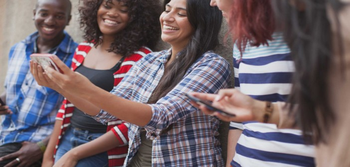 Stock photo of five young adults of mixed genders and races taking a selfie