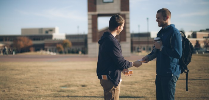 Stock photo of one young white man handing a pamphlet to another young white man in a school's quad