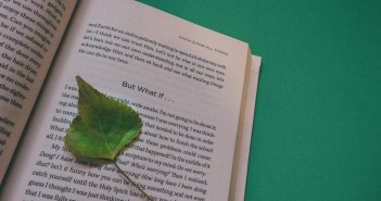 Stock photo of a book opened up to a page with a green leaf marking where the reader left off