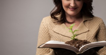 Stock photo of a white woman holding open a book that has a small green plant planted in it