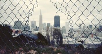 Stock photo of a fence with a hole in it overlooking a city skyline