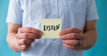"Stock photo of a white person holding a post-it note that says ""LISTEN"""