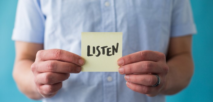 """Stock photo of a white person holding a post-it note that says """"LISTEN"""""""
