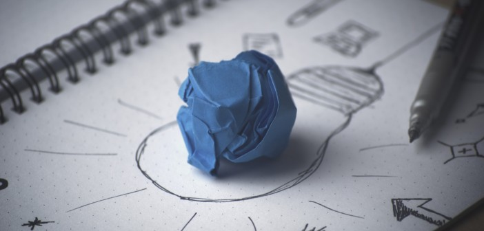 Stock photo of a crumpled up blue piece of paper on top of a drawing of a lightbulb