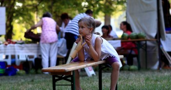 Stock photo of a young white girl sitting on a bench at a community picnic