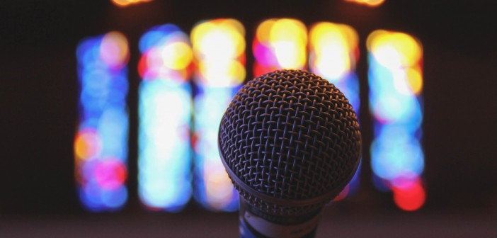 Stock photo of a stand microphone inside a worship space with stained glass windows