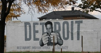 "Stock photo of a white wall with ""DETROIT restaurant and food service"" and a young African American man with his fists up painted on it"