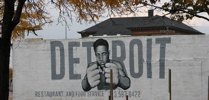 """Stock photo of a white wall with """"DETROIT restaurant and food service"""" and a young African American man with his fists up painted on it"""