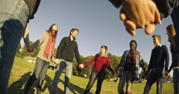 Photo of a diverse group of young adults holding hands in a circle under a blue sky