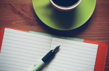 Photo of pen and paper on a table top with cup of coffee