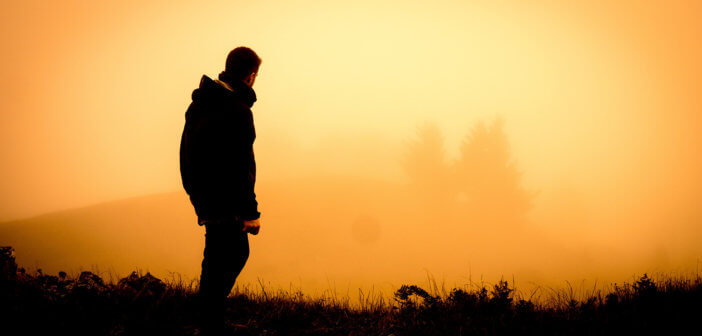 Hiker looking at a beautiful misty sunrise