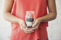 "Photo of a young person holding a glass jar of money marked ""Give"""
