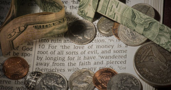Cash and coins lying atop a Bible