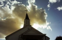 Photo of a church steeple backlit by the sun and clouds