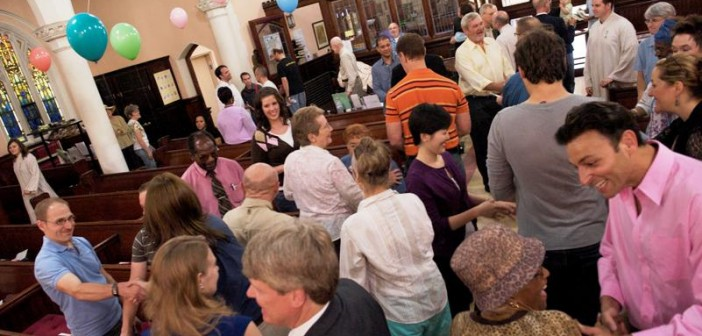 Stock photo of a diverse group of people greeting each other during worship