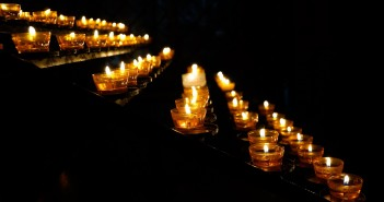 Stock photo of a bunch of lit votive candles in the dark