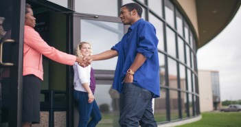 Stock photo of a middle aged African American woman in business attire shaking hands with a younger African American man dressed like a college student at the entryway of a building with a younger white woman holding the door.