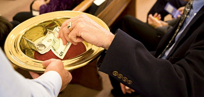 Image of person placing money into an offering plate