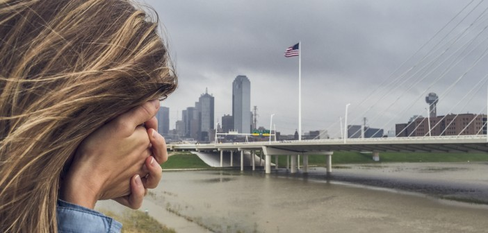 Stock photo of a woman with her face buried in her hand standing by a city waterfront