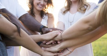 Stock photo of a group of smiling people with their hands all-in in a manner similar to how a sports team would end a huddle