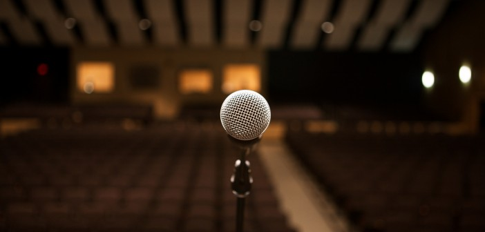 Stock photo of a stand microphone presumably on a stage facing an empty auditorium
