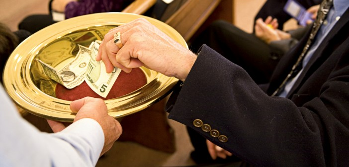 Image of a person placing money in an offering plate at church