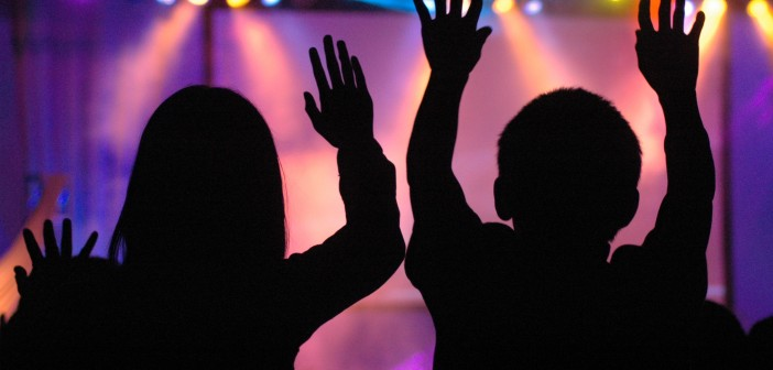 Silhouettes of people worshiping in a contemporary setting