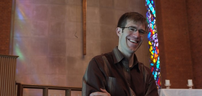Photo of young pastor smiling in a church