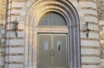 Photo of an arched doorway of a stone seminary building