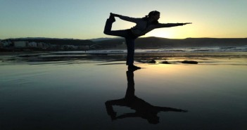 Silhouette of a woman striking a balanced yoga pose on a beach