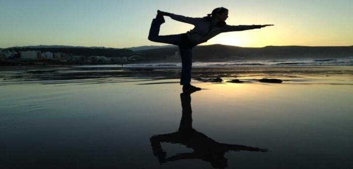 Silhouette of a woman striking a balanced yoga pose on a beach