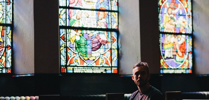 Man sitting alone in a pew in front of stained glass windows