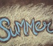 The word SUMMER written in sidewalk chalk against a yellow background