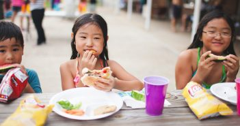 Photo of smiling kids eating at a picnic table