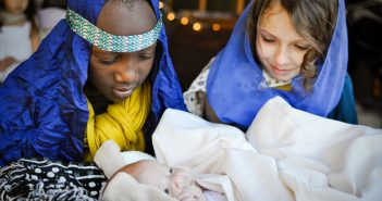 Photo of children playing Mary, Joseph, and baby Jesus in a live nativity scene