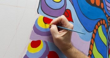 Photograph of someone painting a mural
