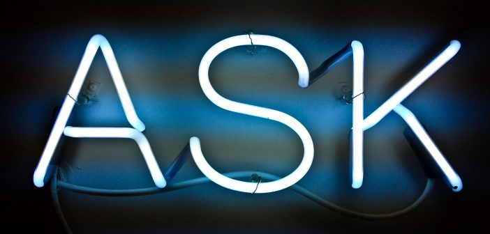 Blue neon sign that says ASK. Asking
