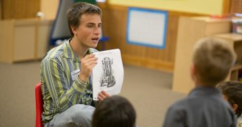 A young adult reading to a group of kids and engaged in his church's partnership with the local school