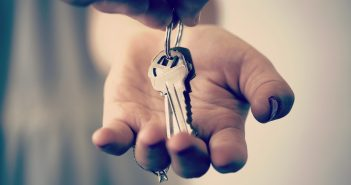 A hand holding a set of keys embarking on one of life's transitions