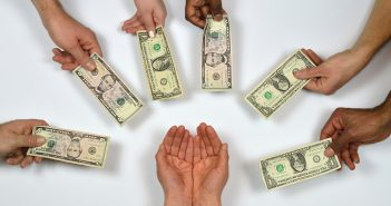 Photo of outstretched hands giving money