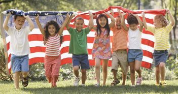 Photo of a diverse group of children running with an American flag, which highlights the coming demographic shift. CREDIT: Ariel Skelley / Blend / Learning Pictures / Universal Images Group