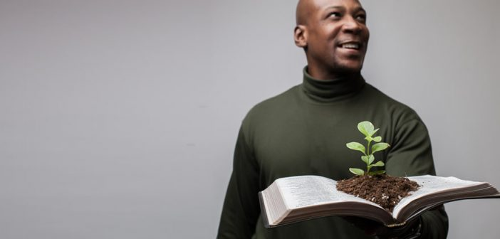 Photo of a person holding an open Bible with a seedling sprouting from the pages