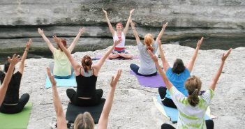 Photo of a group of people doing yoga outside by a stream