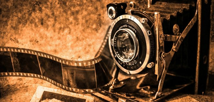 Sepia-toned photo of an old camera, film, and photographs