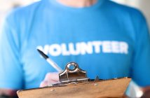 "Photo of a person wearing a ""Volunteer"" t-shirt writing on a clipboard"